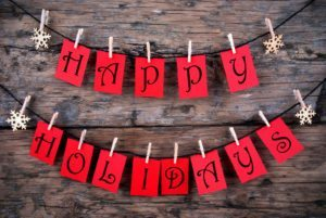 Happy Holidays Greetings on red Tags Hanging on a Line with Snowflakes Christmas or Winter Background